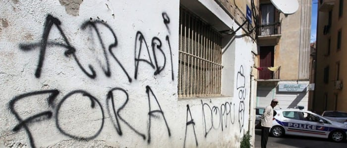 """A police vehicle is parked, on April 9, 2012, outside the prayer room frequented by the Muslim community of Ajaccio, Corsica, following a blaze which was alleged to have been a racist attack in the night from April 8 to April 9, 212.  Following the fire, racist graffiti, in Corsican language, was discovered on the facade of the building, including """"out with Arabs, See you Soon"""" (Arabi fora A boppu), and a depiction of a coffin. AFP PHOTO / PASCAL POCHARD-CASABIANCA"""