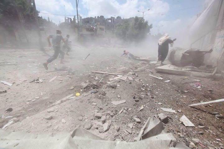 23 juillet 2014 Une femme et quelques passants courent sous un bombardement d'un quartier de Gaza