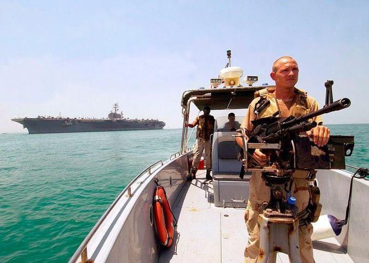 """2 août 2004 : Le porte-avion américain USS John F. Kennedy s'apprête à jeter l'ancre dans le port de Manama. Le navire servait alors de base à l'escadre de chasseurs Carrier Air Wing Seventeen (CVW-17), chargée de mener des missions de support à l'opération """"Iraqi Freedom"""" (""""Liberté en Irak"""")."""