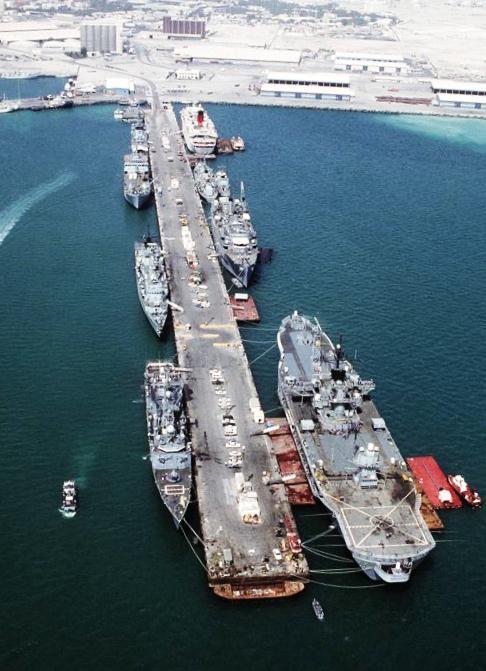 """Des navires de guerre américains dans le port de Manama, au Bahreïn, juste après l'Opération """"Desert Storm"""" (""""Tempête du Désert"""") menée contre l'Irak en 1991. On y voit notamment le navire amiral USS Blue Ridge à droite et la frégates USS Hawes à gauche (ainsi que la frégate britannique HMS Boxer au-dessus)."""