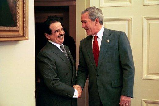 Un an et demi après la photo précédente, le roi du Bahreïn est de nouveau en visite officielle aux États-Unis. Il est ici reçu par le président George W. Bush, hilare, dans le Bureau Ovale le 29 novembre 2004. Il est notable que le roi ne s'habille pas en tenue de cheikh mais en costume occidental lorsqu'il va visiter ses supérieurs hiérarchiques. Soumission symbolique de type vestimentaire à laquelle n'a pas eu droit le pauvre François Hollande.