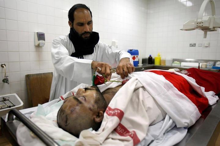 21 février 2011 : Abdulrheda Mohammed est l'un des participants à la manifestation de Pearl roundabout qui ont été tués par les forces gouvernementales. Il a succombé à de très violentes blessures portées à la tête et son corps a été transféré à la morgue du complexe médical Salmaniya. Sur ce cliché terrible publié par le Los Angeles Times, son frère Ahmed Buhmaid vient respectueusement poser une rose rouge sur le corps de son frère défunt.